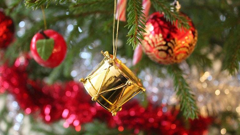 Den guldiga jultrumman tillsammans med annat fint i granen. Foto: Cecilia Osorio/Sveriges Radio