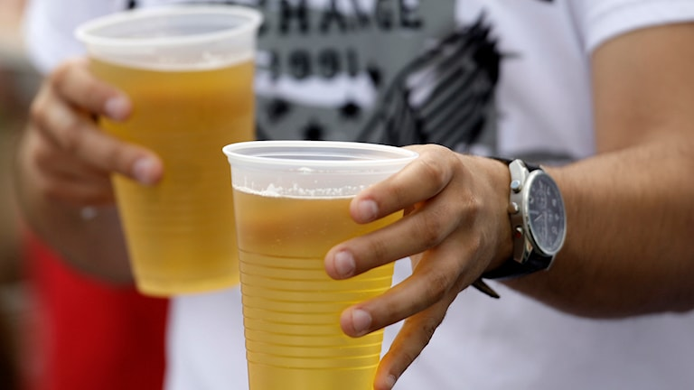En person med två plastmuggar med öl.