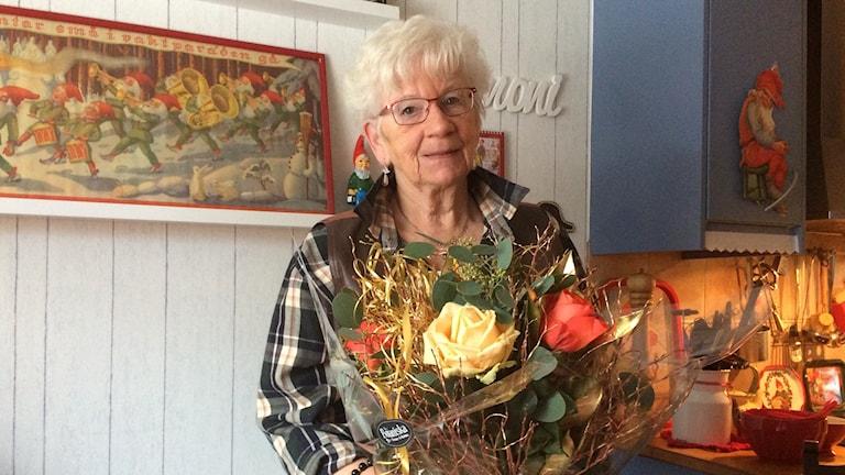 Lena Fogelqwist med en stor blombukett. Foto: Christina Turesson/Sveriges Radio.