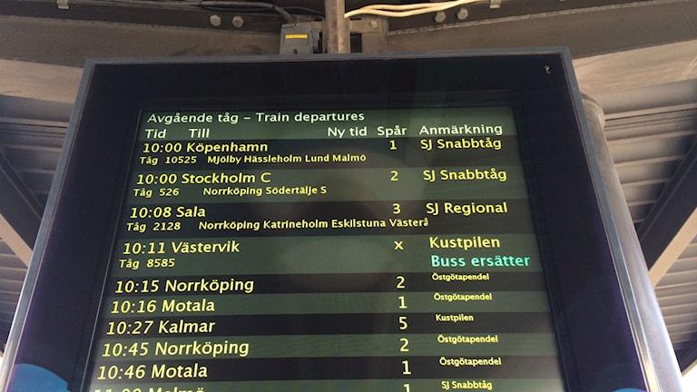 Skylt med text om aktuella tågavgångar och förseningar.
