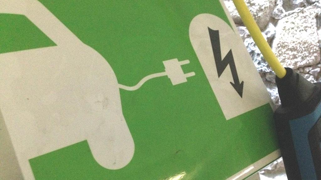 Grön skylt vid laddstolpe för elbil