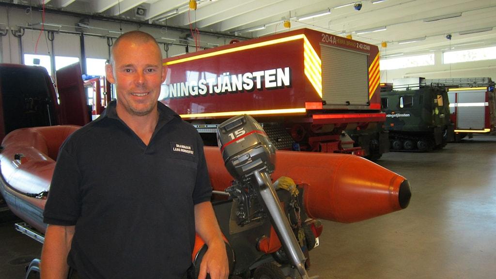 Brandman Lars Nordqvist i brandstationen i Kallerstad med bilar, båt och bandvagn i bakgrunden. Foto: Raina Medelius/Sveriges Radio