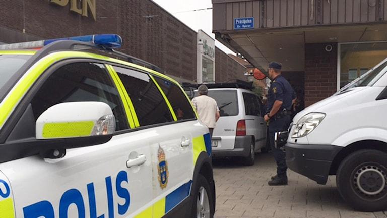 Poliisiauto ja poliisi ruskeiden rakennusten edessä. Kuva: Andreas Åsenheim/Sveriges Radio