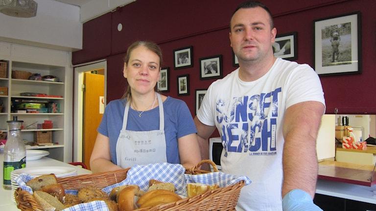 Sofia Mileteg och Amer Veskovic vid en brödkorg på disken i lunchserveringen på Johanneskyrkan. Foto: Raina Medelius/Sveriges Radio