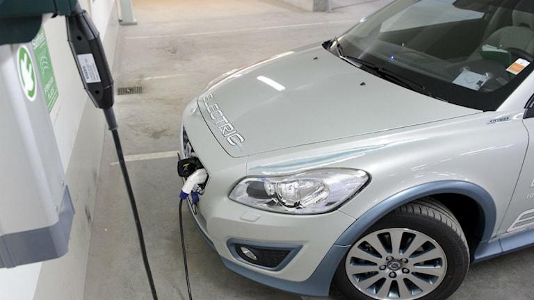 En hybridbil laddas med el på en bensinmack. Foto: Henrik Montgomery/TT