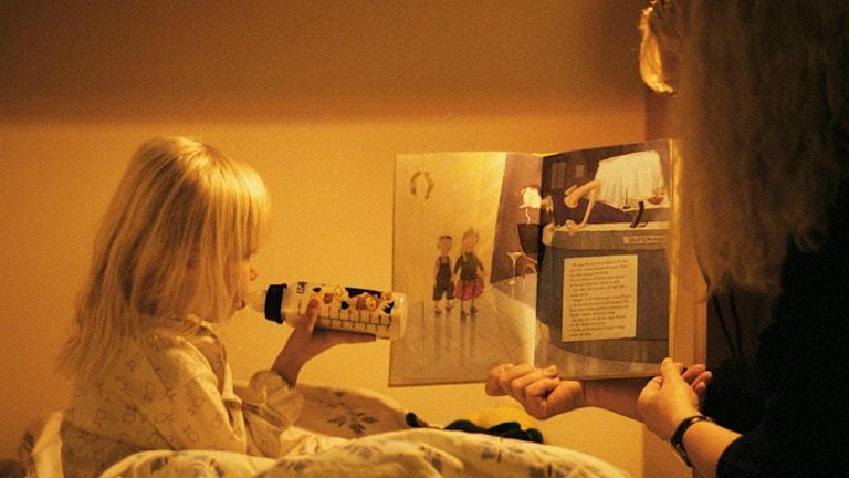 Ett barn dricker välling och kollar i en bok.Foto: Alf Pergeman/TT