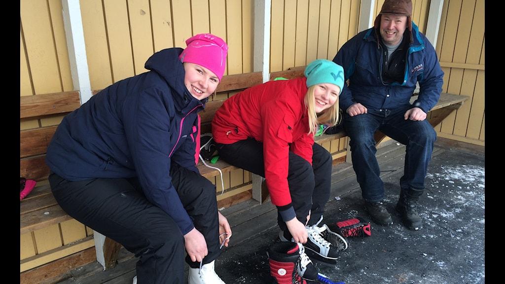 Sofia och Julia Johansson samt Johan Larsson knyter skridskor vid Bollspelaren i Norrköping. Foto: Lisen Elowson Tosting/Sveriges Radio