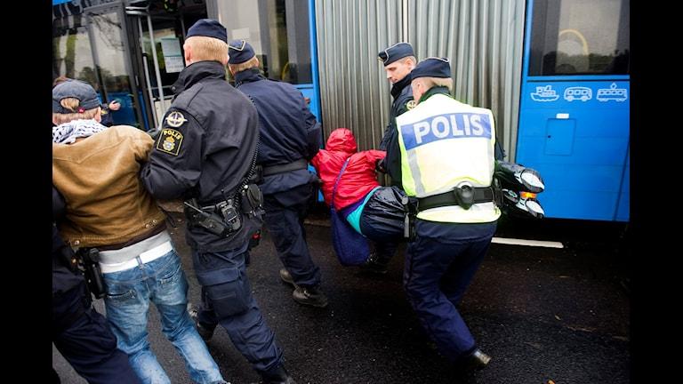 Saraakiil ka tirsan ciidanka ammaanka oo dad khasab ku tarxiileya. Sawirle: Björn Larsson Rosvall/TT