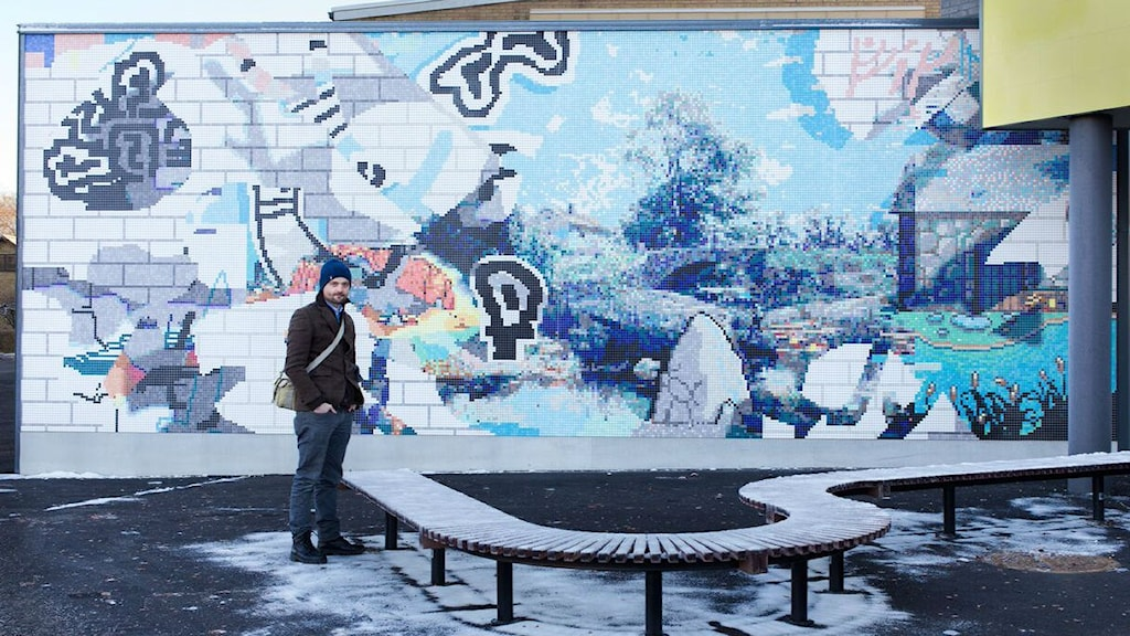 Kristoffer Zetterstrand framför sin väggmosaik Erase to History, som uppförts utanför entrén till Vikingstads nyrenoverade skola Foto: Linköpings kommun