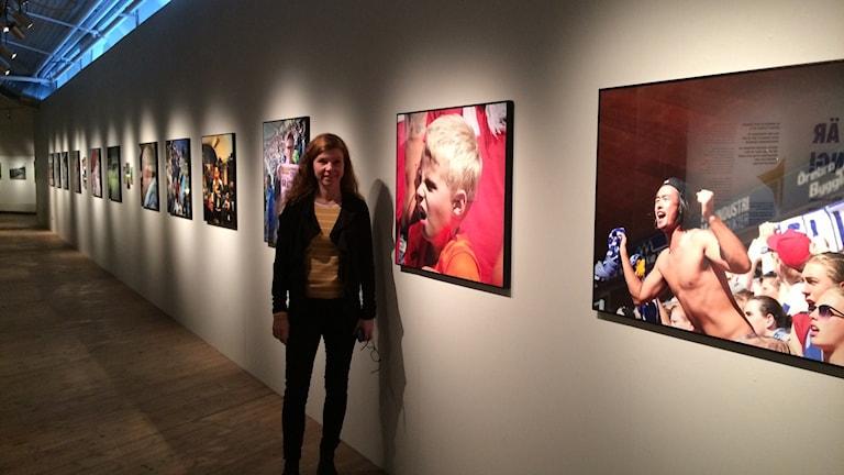 En vägg med bilder och Anneli Egelin Tärning framför. Foto: Malin Marcko/ Sveriges Radio