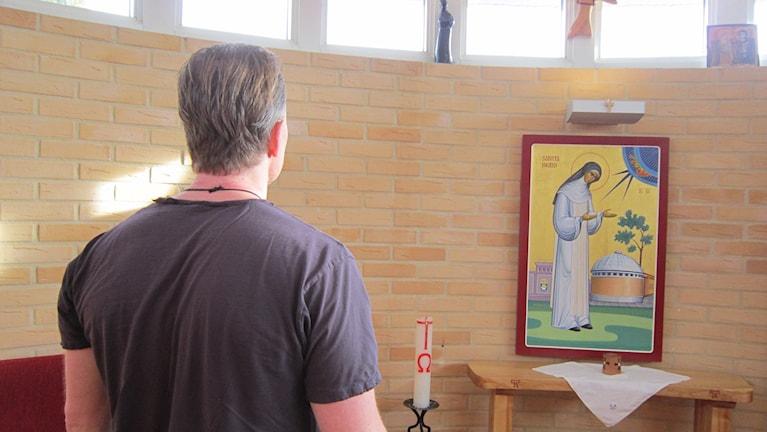 Pepe, en av klosterbröderna på Skänningeanstalten, i klosterkapellet vid en bild av Sankta Ingrid av Skänninge. Foto: Raina Medelius/Sveriges Radio