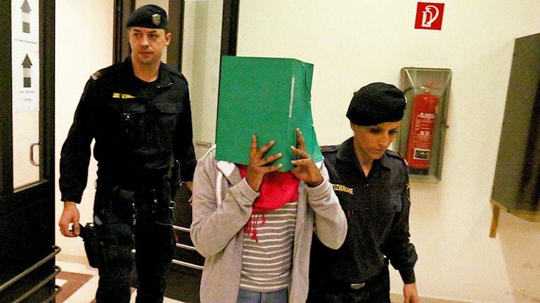 Den terroråtalade flickan på väg in till rättegången i Wien.
