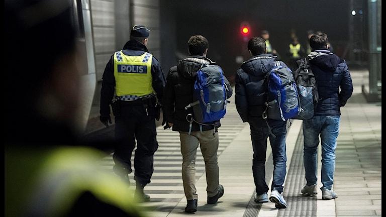 Asylsökande och polis vid en gränskontroll i Skåne.