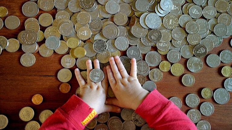 Ett barn leker med mynt.