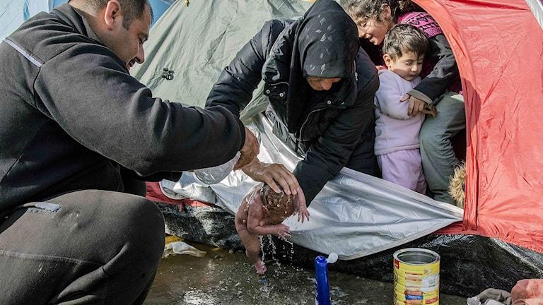 Flyktingkvinna tvingas tvätta sitt barn ovanför en lerpöl i ett flyktingläger i Grekland.