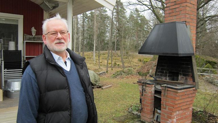Fastighetsägare Lars Enquist i Kinda kommun står i sin trädgård vid en stor murad utegrill.