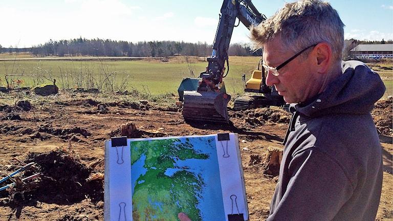 Arkeologen Tom Carlsson visar en karta över Östergötland för 7 000 år sedan.