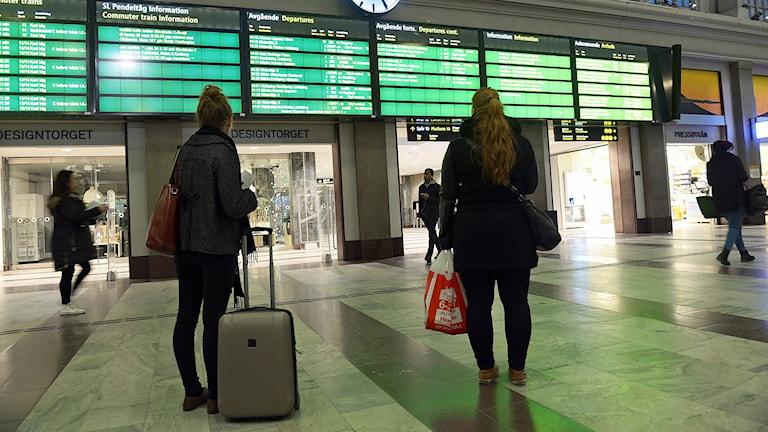 Resenärer som tittar på informationstavlan på Stockholm C.