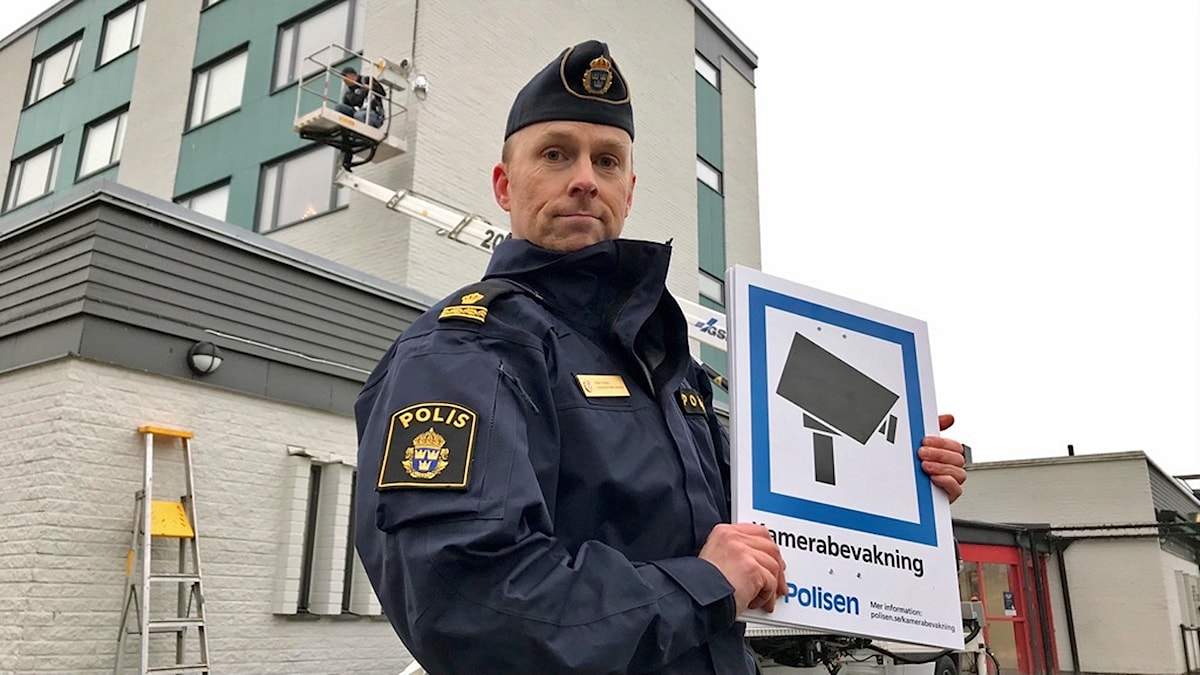 Pär Fridh med en skylt som upplyser om kameraövervakning.