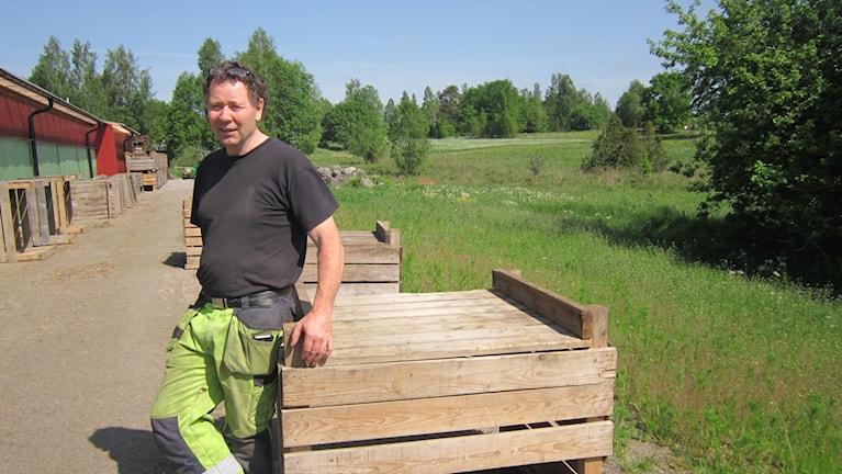Arne Svensson vid kycklingarnas rovfågelskydd som ska ut i den blivande hagen.