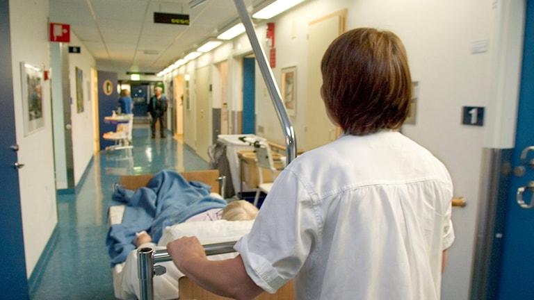 Sjukvårdspersonal rullar sängliggande patient genom korridoren. Foto: Erik G Svensson