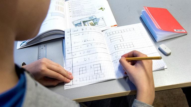 En elev skriver mattetal i sin räknebok.
