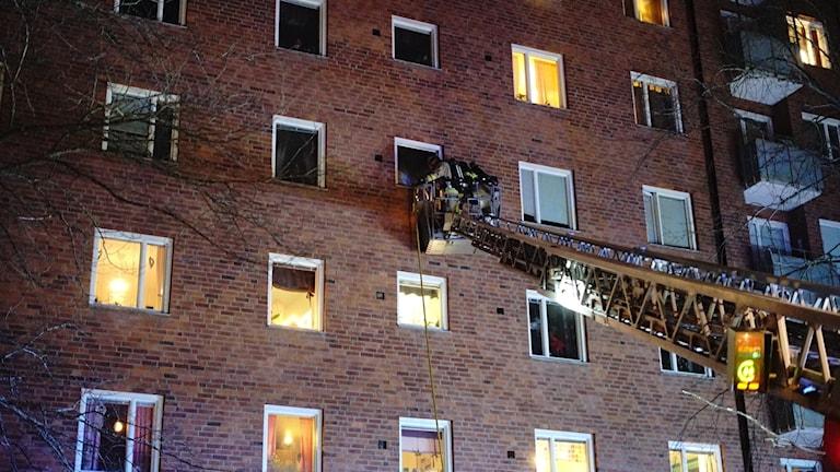 Räddningstjänsten står i en lyftkran för att släcka branden i en lägenhet i Norrköping.