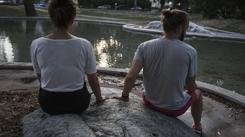Ungt par sitter på en sten med ryggen mot kameran och tittar bort från varandra.
