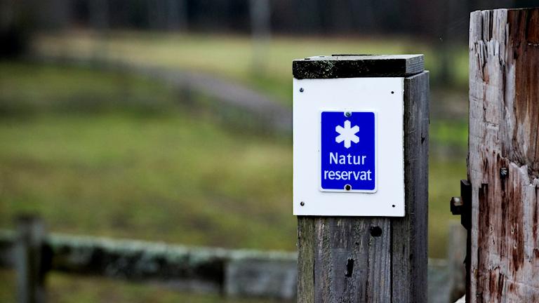 Symbolen för naturreservat på en stolpe.