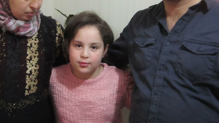 Marwa står mellan sin mamma och styvpappa.