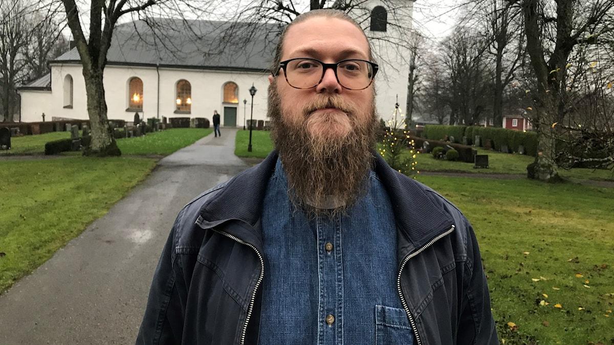 Jacob Sernheim som är präst i Ringarums församling står framför kyrkan i Ringarum.