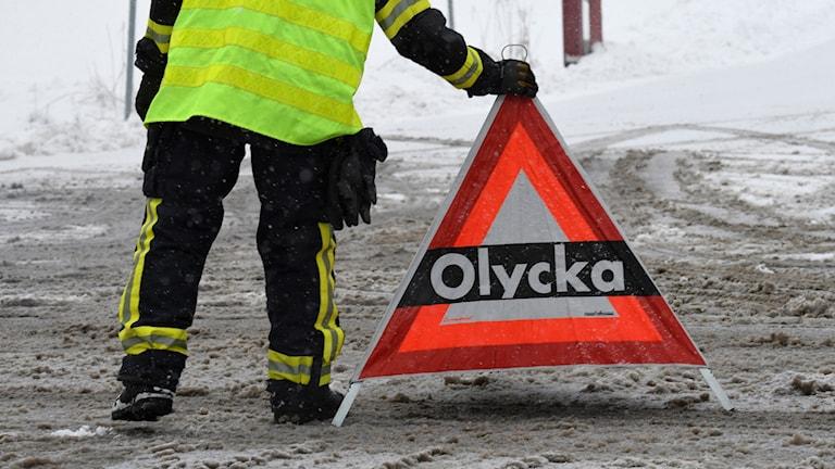 Räddningstjänsten sätter ut en varningsskylt om olycka i vinterlandskap.