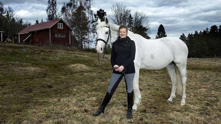 Gertrud Hellbrand står bredvid en vit häst i ett landskap med en röd lada i bakgrunden.