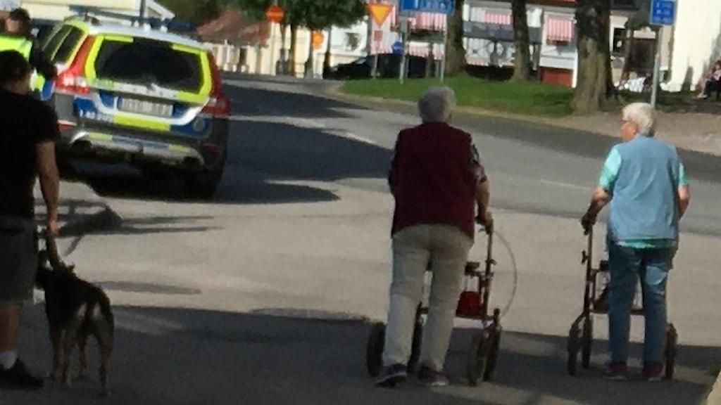 Två damer med rollator står på gatan vid en polisbil i Skänninge.