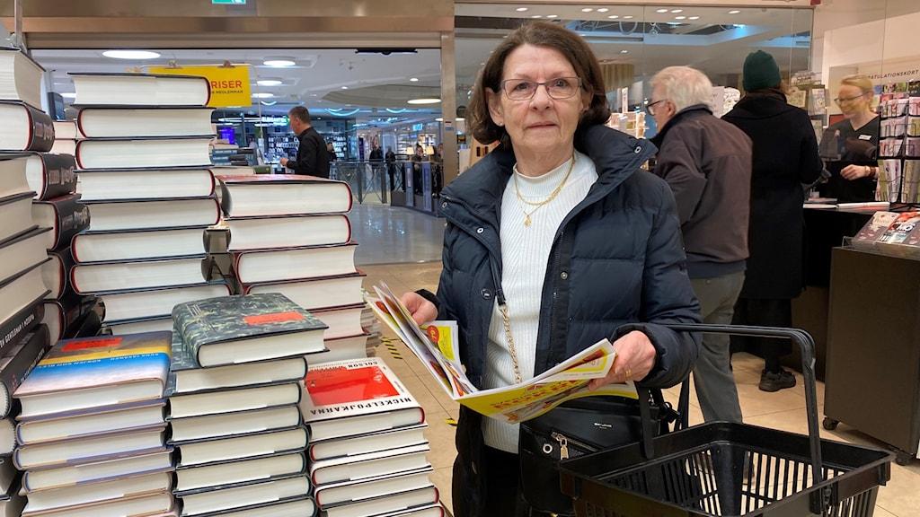 Gun Petersson står vid flera travar böcker på en bokhandel i Norrköping.