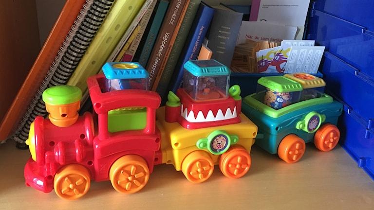 Leksakståg i färgglad plast på lite stökig bokhylla.