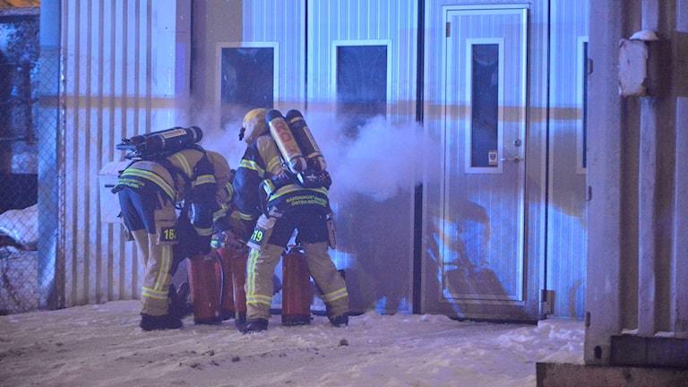 Brandmän utanför en rykande byggnad.