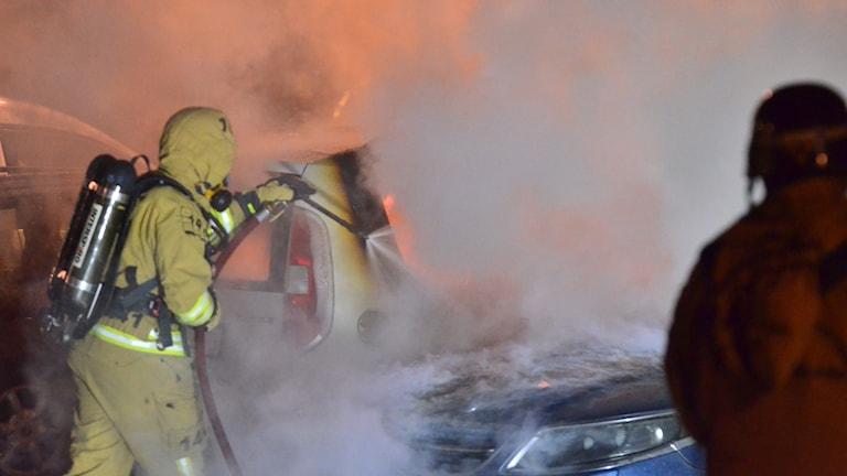 Brandman med tuber på ryggen släcker brinnande bil.