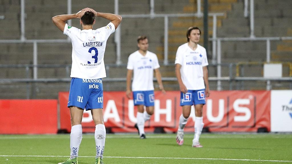 Tre dystra IFK Norrköpingsspelare i sina blåvita matchkläder på planen efter matchen som förlorades mot Häcken. En står med ryggen mot kameran.