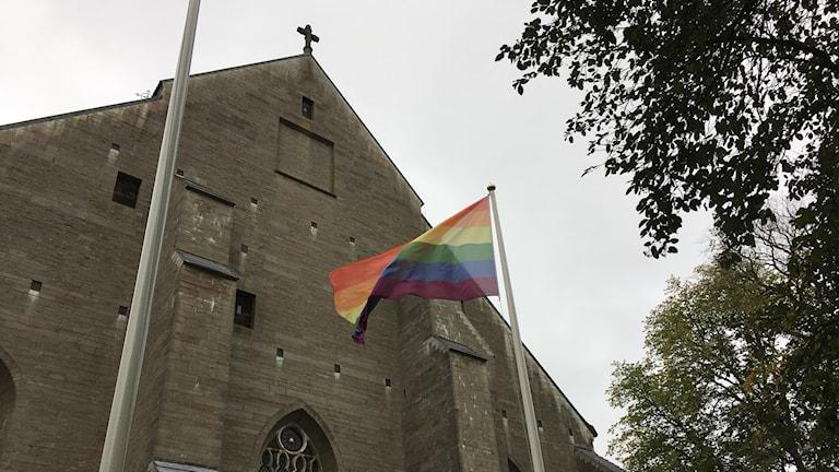 Vadstena klosterkyrka och en prideflagga.