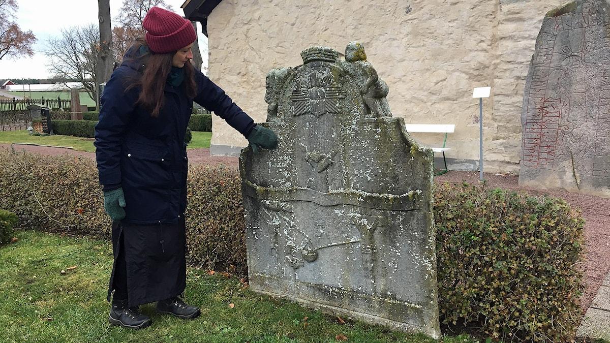 Karin Mårtensson vid en gravsten.