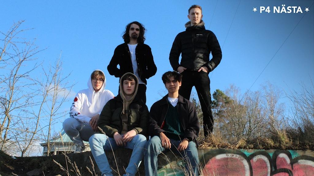 Bilden visar fem killar som står uppradade utomhus.