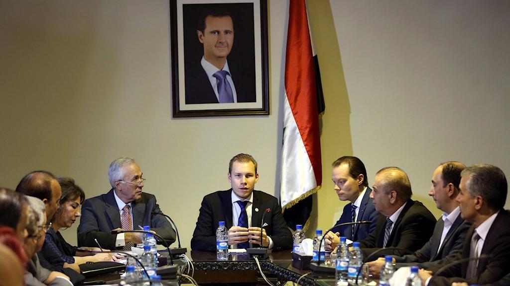 Markus Wiechel sitter vid ett bord med andra människor. Ovanför honom på väggen hänger ett foto av Bashar Al-Assad.