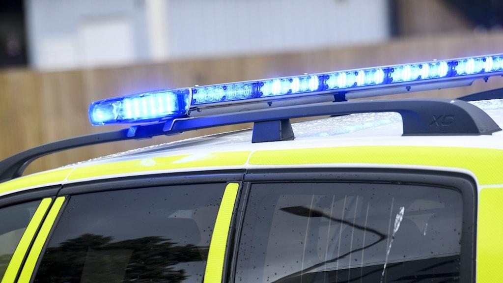 Polisbil i närbild med skinande blåljus på taket.