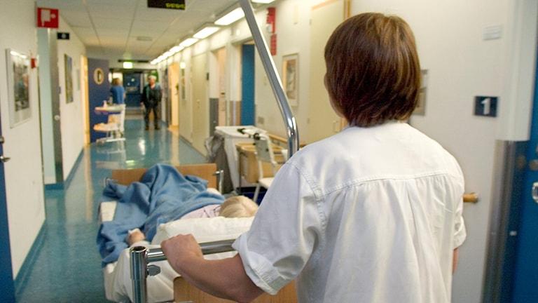 Sjukvårdspersonal rullar sängliggande patient genom korridoren. Foto: Erik G Svensson/TT