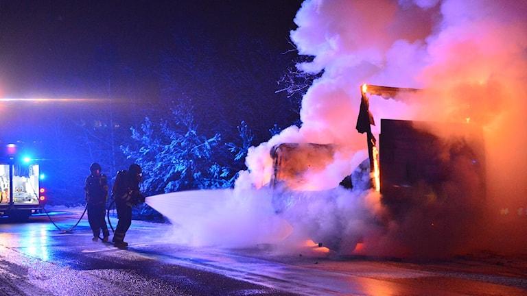 Räddningstjänsten släcker den brinnande skåpbilen.