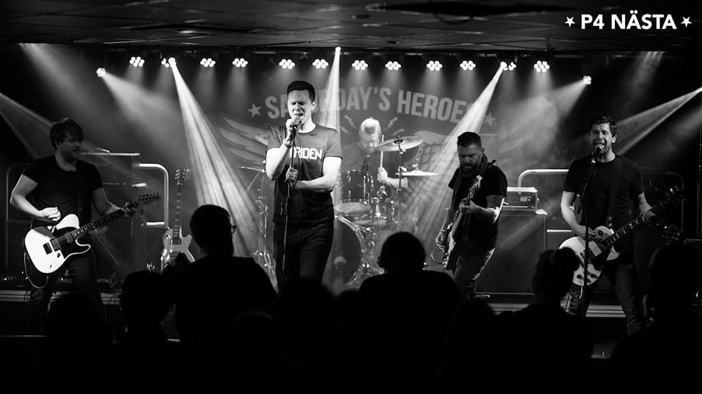 Bilden visar bandet Striden som står och   spelar på en scen.
