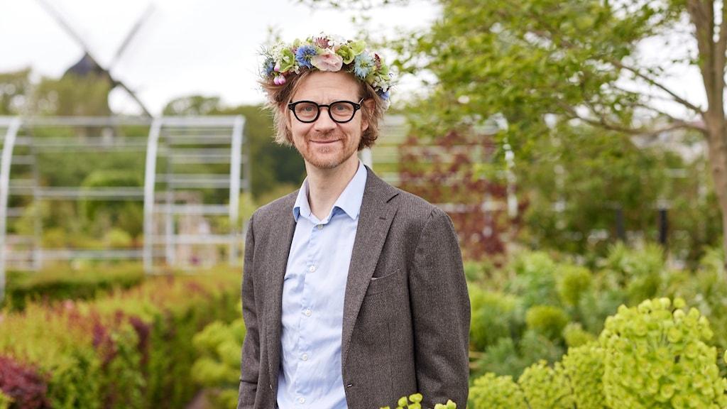 """""""Ankan"""" Johansson i trädgård med krans på huvudet."""