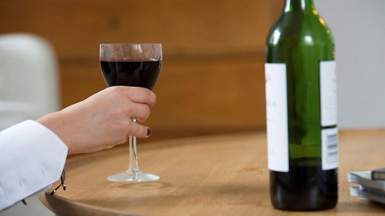 Arrangerad bild på en kvinna som dricker vin i ensamhet. Arkivbild: Fredrik Sandberg/TT
