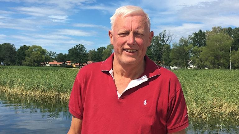 Sportfiskare Göran Ingvald vid Roxen. Vass i bakgrunden och avlägsen bebyggelse skymtar nära vattnet.